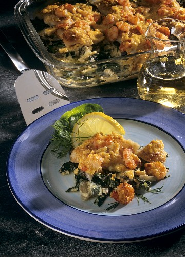 Cod gratin on chard with shrimps on plate and in dish