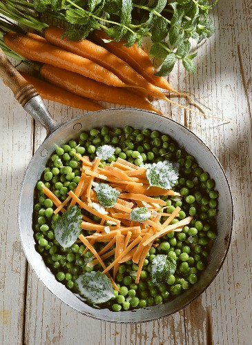 Pea and carrot casserole & mint leaves in pan with handle