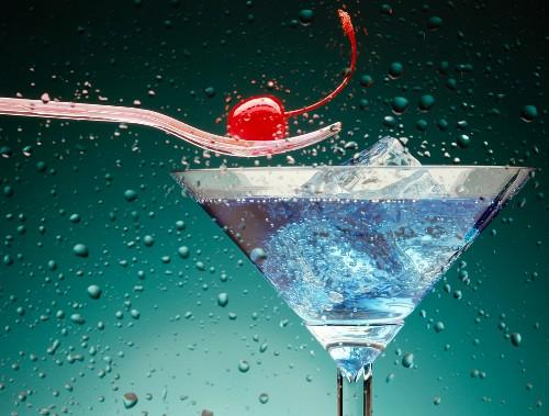 Blue Lagoon im Cocktailglas, darüber Kirsche auf Gabel