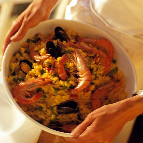 Hands holding a dish of paella