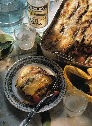Moussaka in cooking dish and on plate; Ouzo bottle