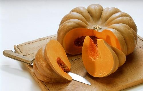 A cushaw pumpkin, cut into, lying on a board