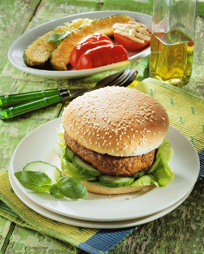 Hamburger with cucumber slices and lettuce leaves