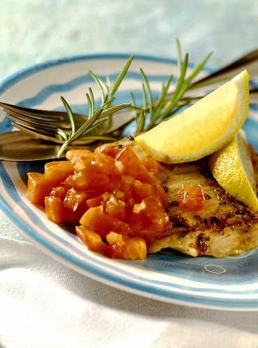 Fried catfish fillet with diced tomatoes and lemon wedges