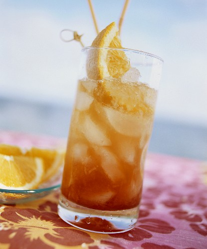 Planter's punch in glass with straws and orange wedges