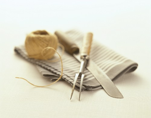 Meat fork, knife and kitchen string on kitchen cloth
