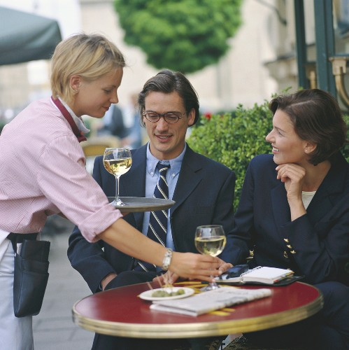 Waitress serving a couple with white wine in open air