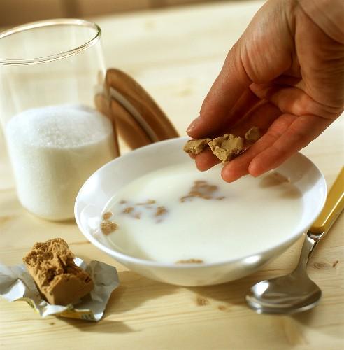 Crumbling yeast into sweetened luke-warm milk