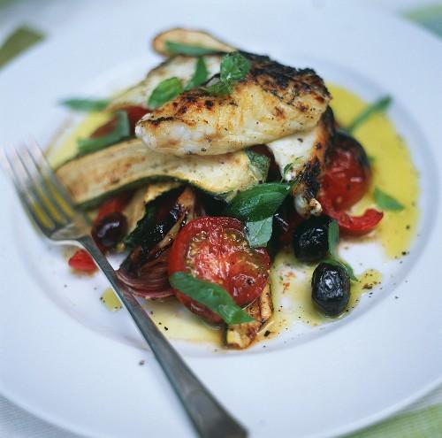 Oven-baked fish fillet on summer vegetables