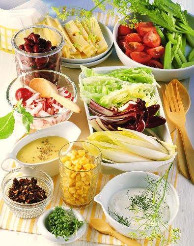 Salad bar with sauces, raw vegetables, cheese & salad leaves