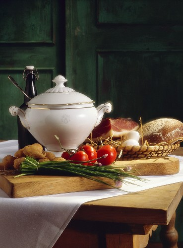 Rustic still life with soup pot, vegetables, bread & bacon