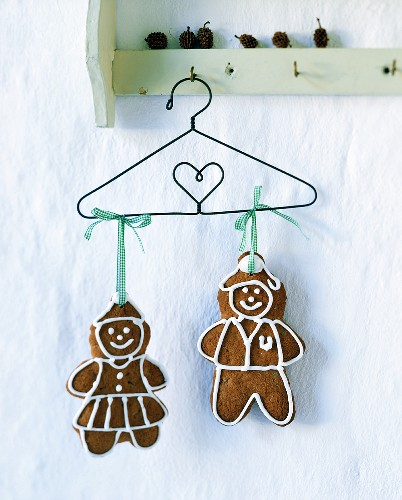Two gingerbread figures hanging on a wire coat-hanger