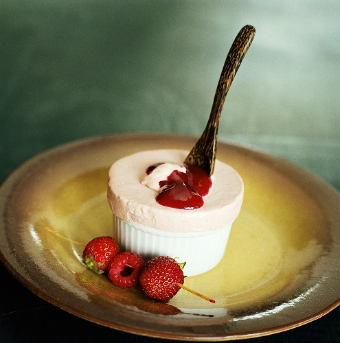 Strawberry ice cream soufflé with berry sauce in mould