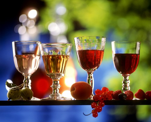 Four home-made liqueurs in glasses