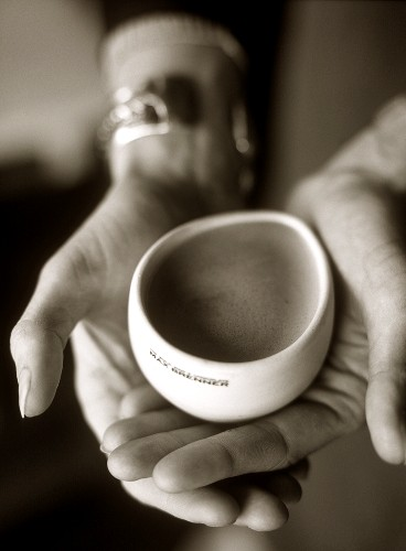 Hand holding drinking bowl of hot chocolate