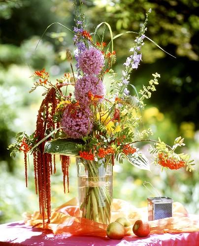 Blumenstrauss mit Allium und Beeren in Glasvase