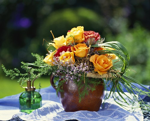 Bouquet of orange and red roses in terracotta vase
