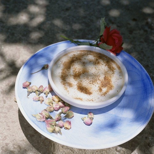 A bowl of cinnamon pudding decorated with flowers