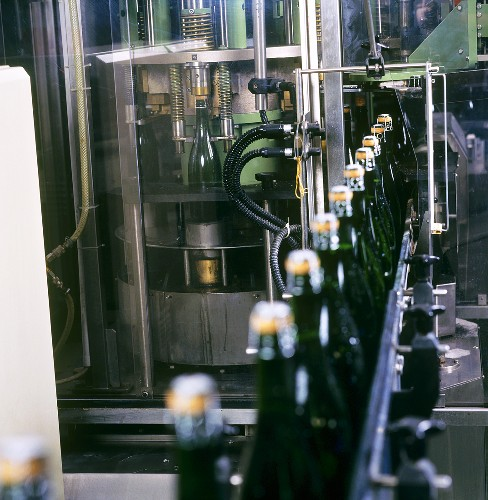 Putting agraffe (wire) on sparkling wine bottles by machine