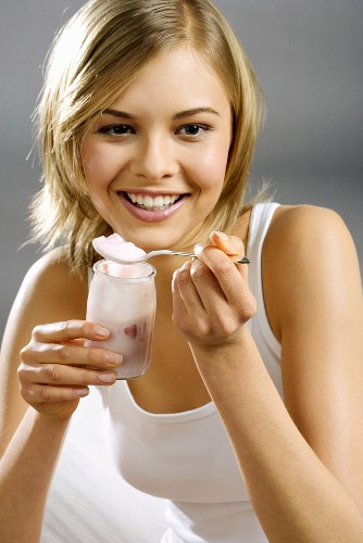 Young woman with yoghurt jar and spoon