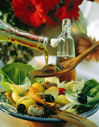 Pouring oil on wooden spoon with olives over vegetable salad