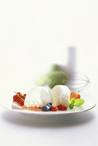 Lime yoghurt parfait on plate with berries and mint leaf