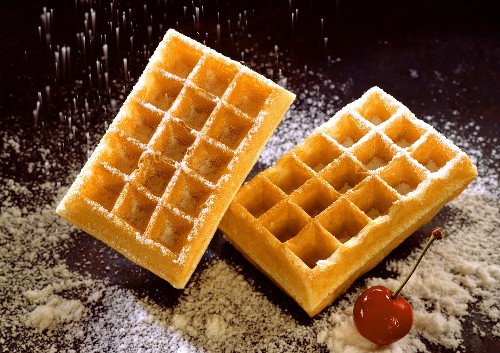 Two waffles being sprinkled with icing sugar, a cherry nearby