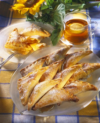 Apricot pasties with icing sugar; tea