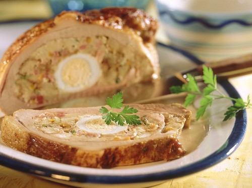 Veal breast with bread roll stuffing and egg, carved