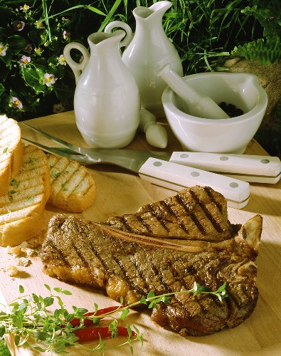 T-bone steak on wooden chopping board with toasted white bread