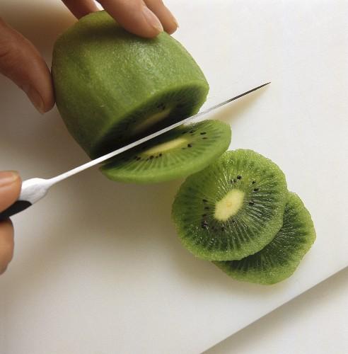 Slicing peeled kiwi fruit