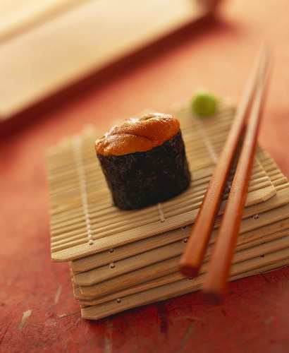 A gunkan maki with sea urchin on bamboo mat with chopsticks