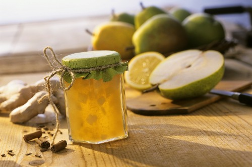Pear jam with ginger and cinnamon in jar; ingredients