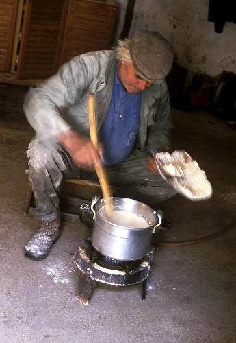 Corsican farmer cooking polenta on small gas stove