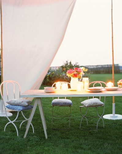 Table in pavilion with candles & flowers for romantic evening
