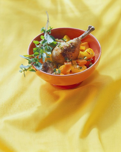 Chicken leg with almonds, vegetables and sprig of oregano