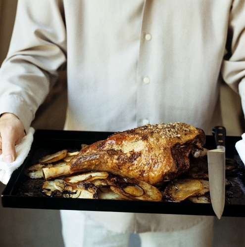 Person holding baking tray with roast leg of lamb