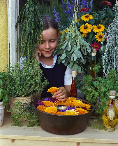 Girl at window with flowers, herbs and herb oils