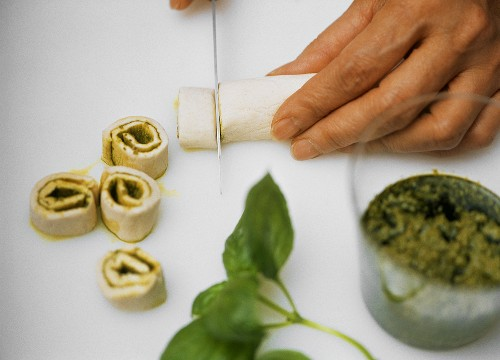 Making small puff pastry coils with pesto