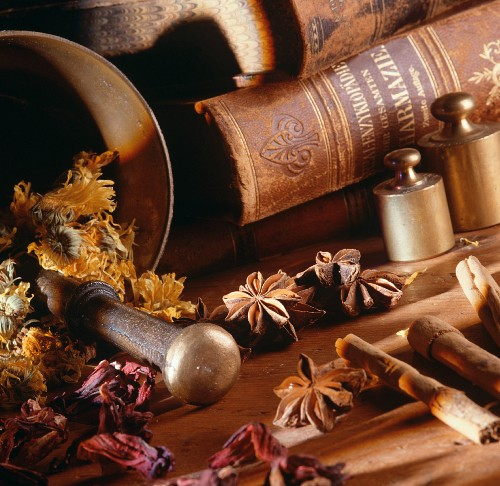 Still life with spices, herbs, mortar and books