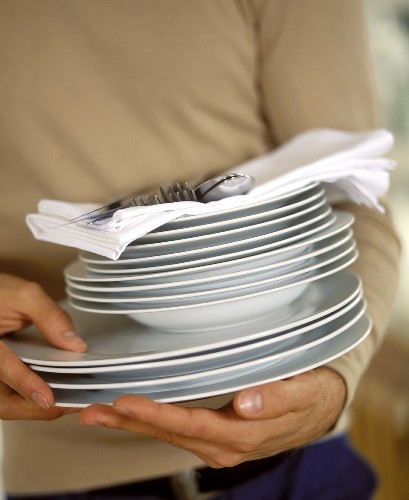 Pile of plates with napkins and cutlery