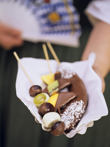 Woman in national dress with chocolate-coated fruit kebab