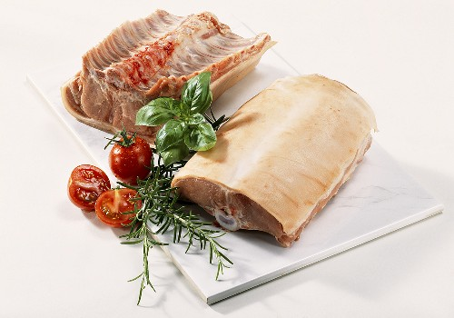 Suckling pig back joint on chopping board with tomatoes & herbs