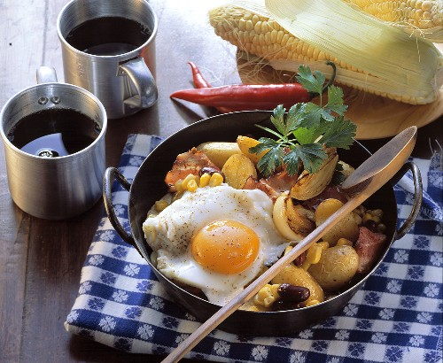 Pan-cooked potato and vegetable dish with fried egg