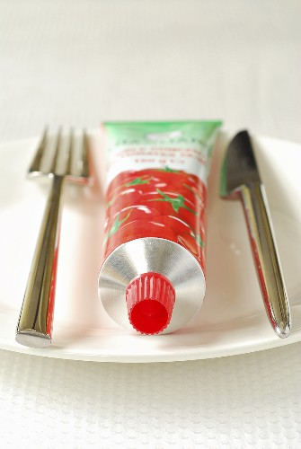 Tomato puree in tube on plate with knife and fork