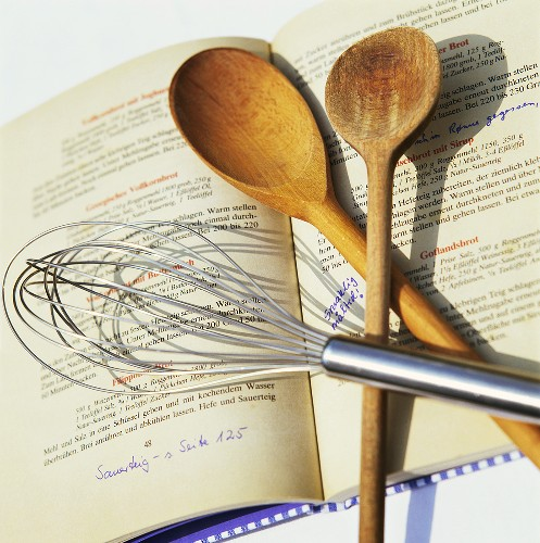 Whisk and wooden spoons on recipe book