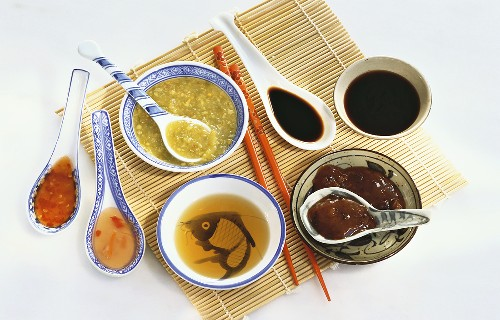 Various Asian sauces in bowls and on spoons