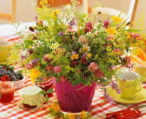 A vase of colourful meadow flowers on breakfast table
