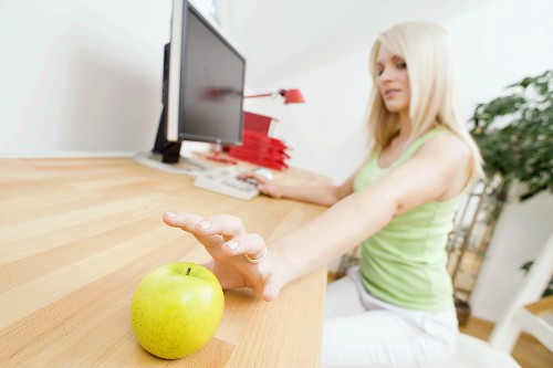 Woman reaching for an apple on her desk