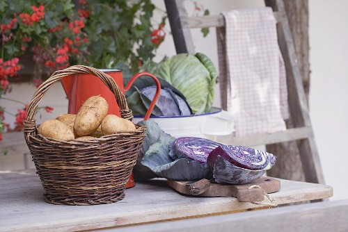 Rustic still life with potatoes & cabbage in front of farmhouse